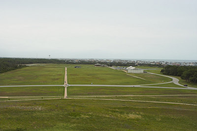 A view from the top of the dune shows all of the Wright Brothers National Memorial.  The closest buildings (far right) commemorate the 100th anniversary of their 1st flight.  The Atlantic Ocean is on the horizon.