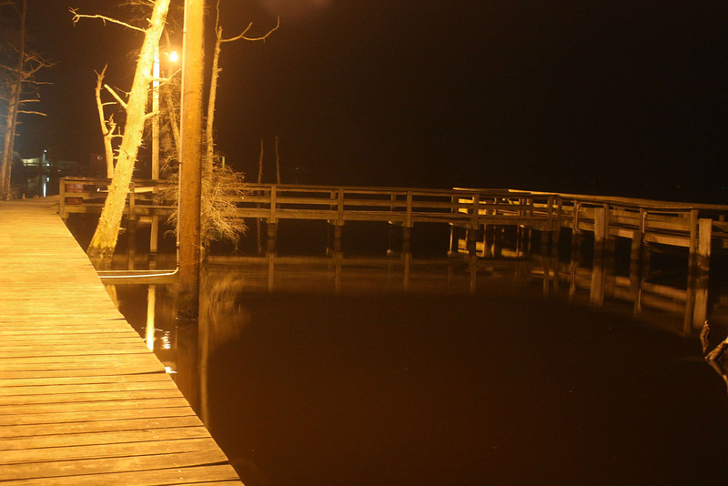 The water is so satiny smooth that it provides a clear reflection of this fishing pier on Albermarle Sound, Elizabeth City, North Carolina