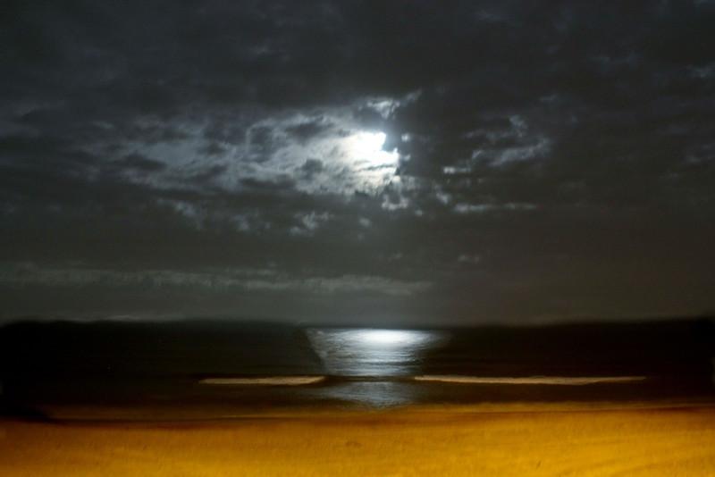 Digitally manipulated of a full moon casting light over the Atlanta ocean, Kill Devil Hills, NC