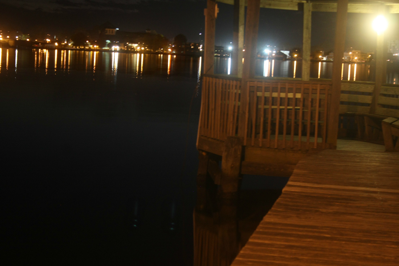 A fishing pier is illuminated by soft lights casting reflections on the quiet waters of Albermarle Sound with the lights of Elizabeth City waterfront in the background.
