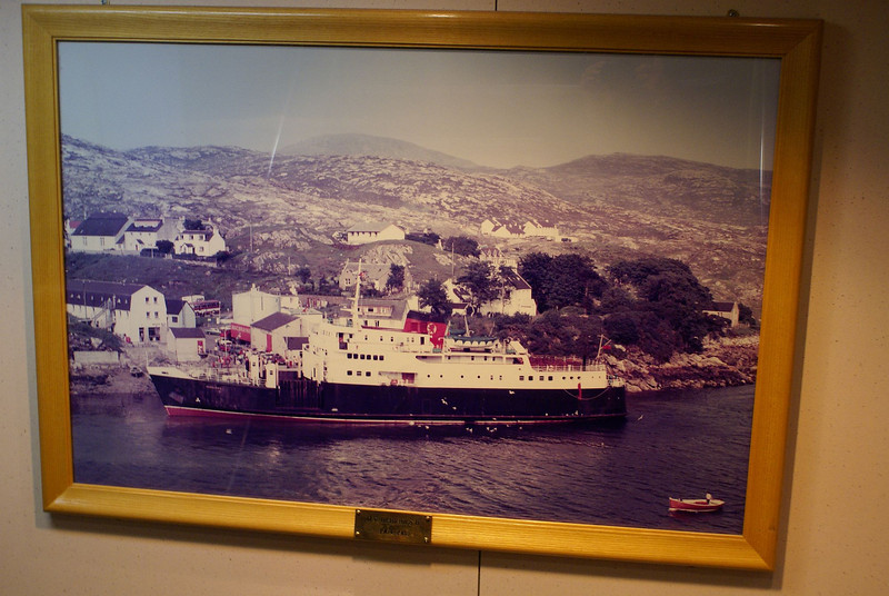"We crossed from Uig on Skye to Lochmaddy on North Uist on MV Hebrides, the third 'MacBrayne' vessel to bear the name Hebrides. Aboard it was great to see this picture of the second Hebrides berthed at Tarbert, Harris. It was aboard that ship that we had started our first family tour of the islands of Lewis and Harris in 1972<br /> <br /> The vast majority of the ships that had served the Firth of Clyde and the Scottish Highlands and Islands in the near two centuries that had past since the pioneering paddle steamer Comet had first appeared in 1812, had been built in one of 40 or more shipyards that used to line the banks of  the River Clyde and I had taken a great interest in watching many of the most recent ships (from the 1960s onwards) being constructed, then sailing on them during their susbequent years of service in Scottish waters. Sadly, this third Hebrides, which was built at the Ferguson shipyard in Port Glasgow, seems destined to be one of the last 'Clyde-built' ships to serve on Scotland's coastline; effectively by the middle of the first decade of the 21st Century, merchant shipbuilding on the Clyde had ceased. The many shipyards on the Clyde, which had built over 25,000 ships in the preceding three centuries was reduced to just two, producing (at best)  one or two ships a year (compared to over 370 that had been completed in the single calendar year of 1913). Although Her Majesty Queen Elizabeth had come to Clydeside on many occasions to sponsor and launch new ships, the third Hebrides was the first vessel of the famous Caledonian MacBrayne fleet to be launched by her, or indeed, by any reigning monarch - a fact that is commemorated in the ship's observation lounge - see picture at the following link which was taken during my first sailing on the third Hebrides in August 2003<br /> <br />  <a href=""http://pudzeoch.smugmug.com/Ships/Scottish-Coasts-and-Shipping/1758734_qf5Jg#108499959_iv3kN-A-LB"">http://pudzeoch.smugmug.com/Ships/Scottish-Coasts-and-Shipping/1758734_qf5Jg#108499959_iv3kN-A-LB</a><br /> <br /> A splendid picture of the first Hebrides, a traditional steamship that had been built at A & J Inglis Pointhouse shipyard in Glasgow, while berthed in the Kingston Dock in her native city (a dock that is now infilled and almost forgotten), is also displayed prominently aboard her current successor- see it at<br /> <br />  <a href=""http://pudzeoch.smugmug.com/Ships/Scottish-Coasts-and-Shipping/1758734_qf5Jg#108499623_tV8xB-A-LB"">http://pudzeoch.smugmug.com/Ships/Scottish-Coasts-and-Shipping/1758734_qf5Jg#108499623_tV8xB-A-LB</a><br /> <br /> Also, the traditional brass bell of Hebrides (I), which was subsequently carried aboard Hebrides (II) during her period on the service between Skye, North Uist and Harris, is given pride of place on the current vessel. During the period from 1985 to 2001, when there was no vessel called Hebrides in the CalMac fleet, the bell had been proudly displayed in the Harris Hotel at Tarbert - see a picture of it at<br /> <br />  <a href=""http://pudzeoch.smugmug.com/Ships/Scottish-Coasts-and-Shipping/1758734_qf5Jg#108499301_CpfJE-A-LB"">http://pudzeoch.smugmug.com/Ships/Scottish-Coasts-and-Shipping/1758734_qf5Jg#108499301_CpfJE-A-LB</a>"