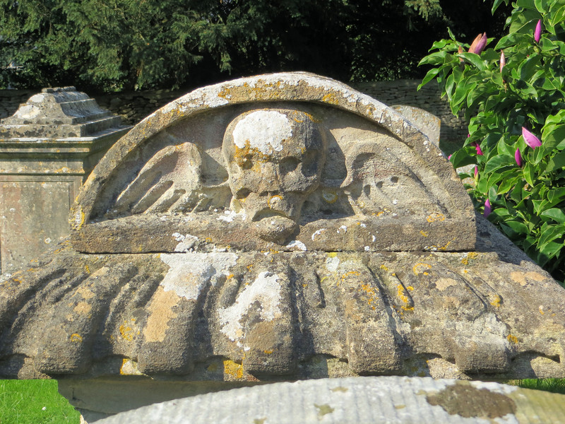 Carvings on headstones run in fashions like anything else.  From observation I would say that death's head like this, cherubs, and fruits and flowers, were popular in the Cotswolds in the 17th century.