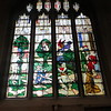 In an age when few people could read, and the Bible wasn't available in English anyway, stained glass windows performed the function of teaching people Bible stories.  This window is called The Fall and has 4 parts, from left to right:  Eve is taking the forbidden fruit from a blue (!) serpent; Moses sees God in the Burning Bush; Gideon and the Fleece; The Queen of Sheba is offering a silver casket to Solomon.