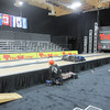 """Brunswick makes a portable bowling alley that can include one or more lanes.  This PBA event requires two lanes.  Notice the machine that cleans the alley and applies an oil pattern.  These alleys mimic standard """"fixed"""" lanes in every way.  The ramp allows bowlers to get their rolling cases up into the approach area."""