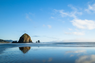 Haystack rock reflected in wet sand of ocean beach