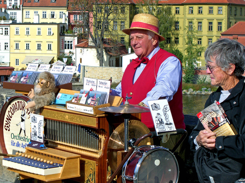 An organ grinder among the many vendor stalls on the bridge.