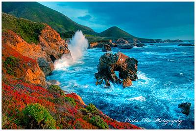 Waves crash the rocky shoreline hard at sunset.