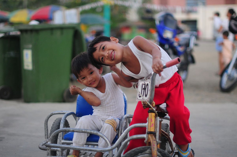 "Little Filipino boys have fun on rented trikes at Puerto Princesa's popular <a href=""http://purpleslipperz.blogspot.com/2014/01/puerto-princesa-palawan-city-baywalk.html"">Baywalk</a>. No doubt the older one fancies himself to be driving one of the life-sized motorized trikes these boys have seen men driving around town."