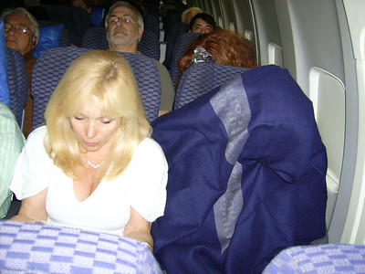 On the plane we settle in.  Here's Suzi with her carryon, boyfriend in a bag. (Yes John G.'s in the cocoon stage).