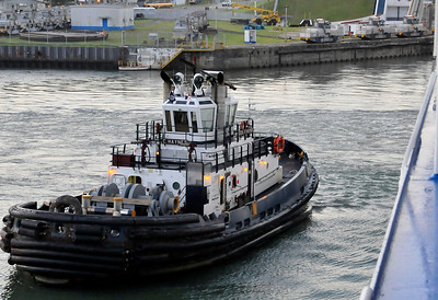 A tug gets ready to push the ship to line it up to start through the first lock.