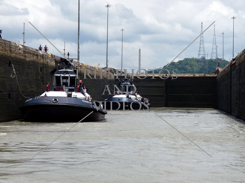 Panama Canal lock chamber being flooded while tug boats await to transit the canal.
