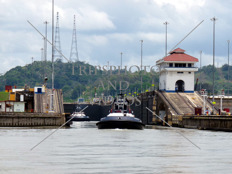 Boats exiting a lock chamber by the control house at the Panama Canal.