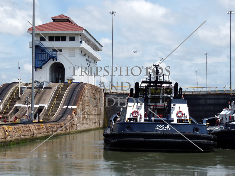 A control house and boats waiting at the lock chamber while on transit at the Panama Canal.