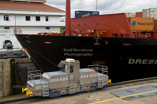 Electric locomotives, so called mules, guiding a large container vessel into the lower chamber of the Mirflores Locks; Panama Canal, Panama City, Panama