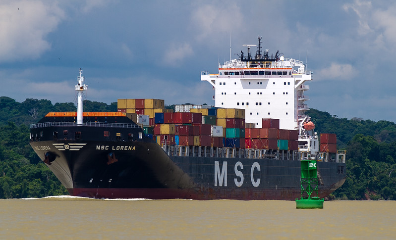A massive ship passes through the Panama Canal. In the background you can see how close the rainforest is to the canal.