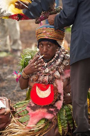 A woman smokes while her feathers are being attached