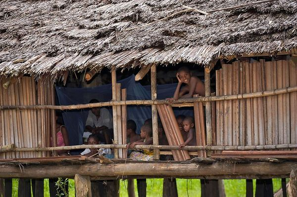 Villagers watch the sing sing from the comfort of their house