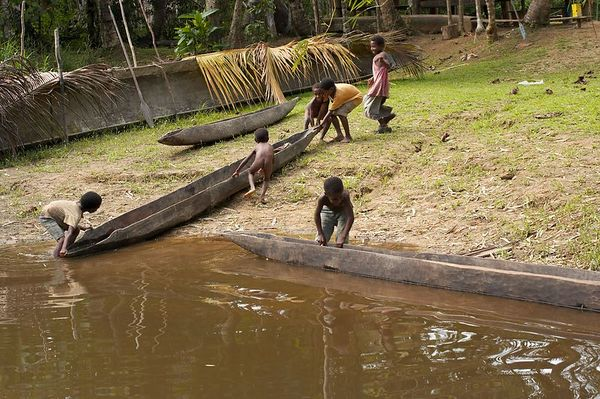 Kids pull in a canoe from the river