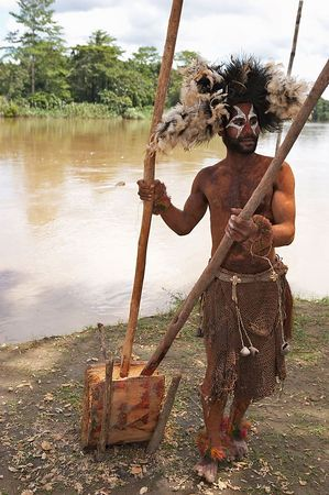 Sago-making demonstration.  Man removes bark from sago palm.