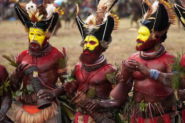 The mighty Huli, with traditional yellow faces and red body paint.  Traditional paints are much less bright (we saw this in Huli country)