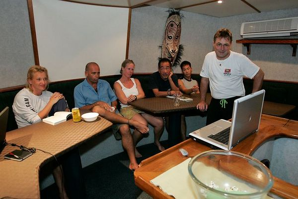 Anita, Jack, Denise, Toshi, Son, and Lucien watch footage from French Polynesia