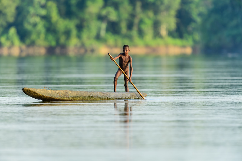 Daily life in the remote area of Papua New Guinea - Young boy and a dugout canoe was taken in Kawari, East Sepik, Papua New Guinea.