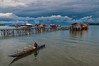 An Ambai man paddles his canoe in to shore as a violent storm approaches from the south. Warironi, Papua, Indonesia. [Papua Warironi 2013-04 001 YapenIs-Indonesia_TC]