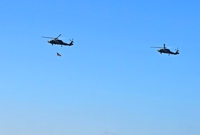 MH-60 Helos bring in the Flag