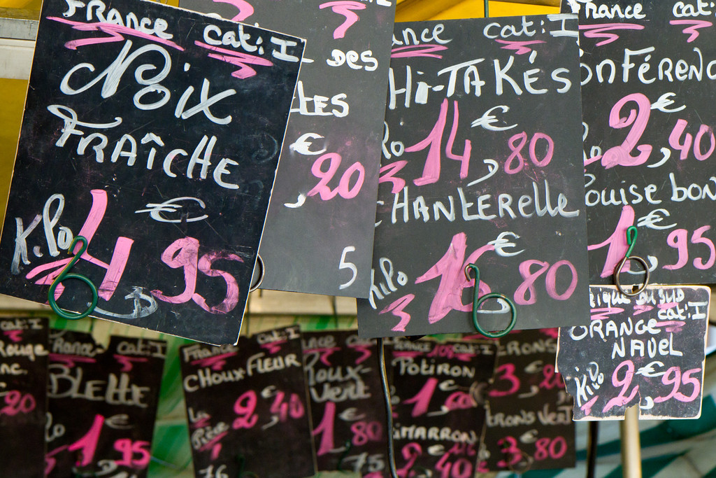 In the farmers market signs displayed the wares, their site of origin, and their price.