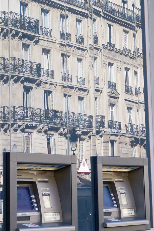 Old and new- an apartment from the 1800's is reflected in the windows of a newer building with ATM's