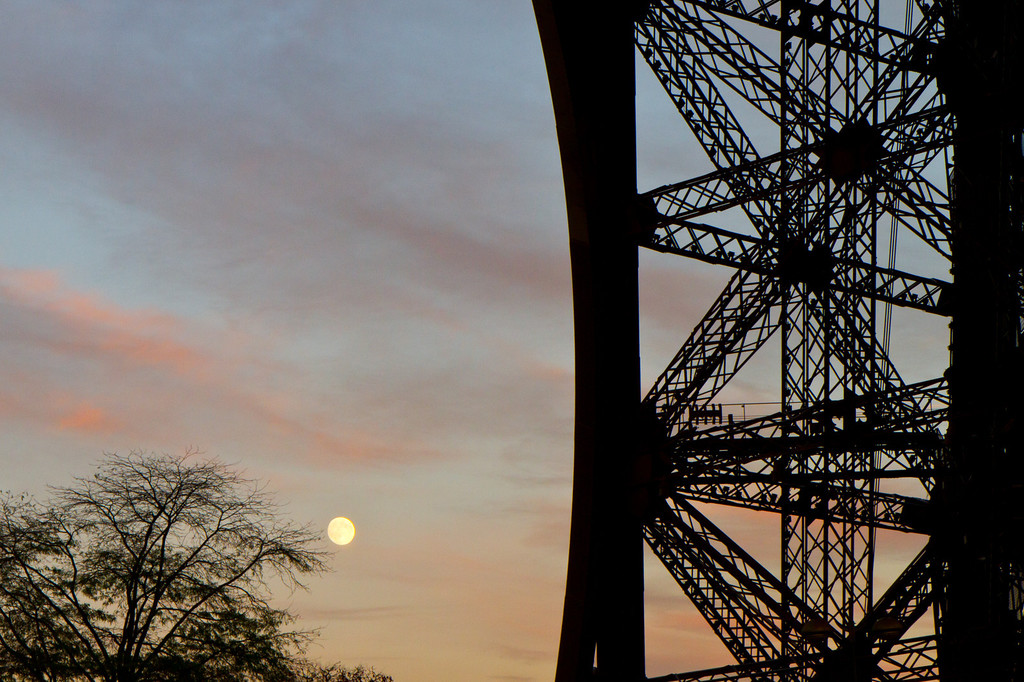 Rising moon at sunset against a leg of the Eiffel tower