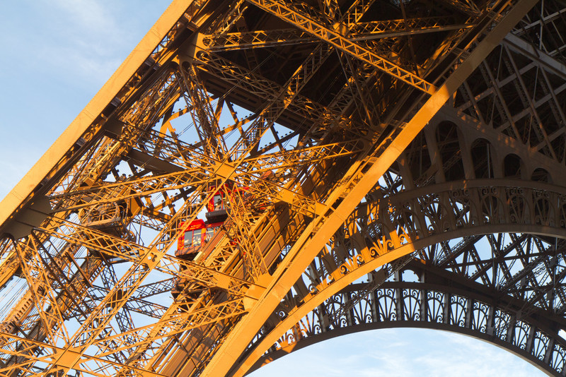 Along one leg of the Eiffel tower, elevators take visitors to the upper decks. These twin level elevators hold 50 or more people each