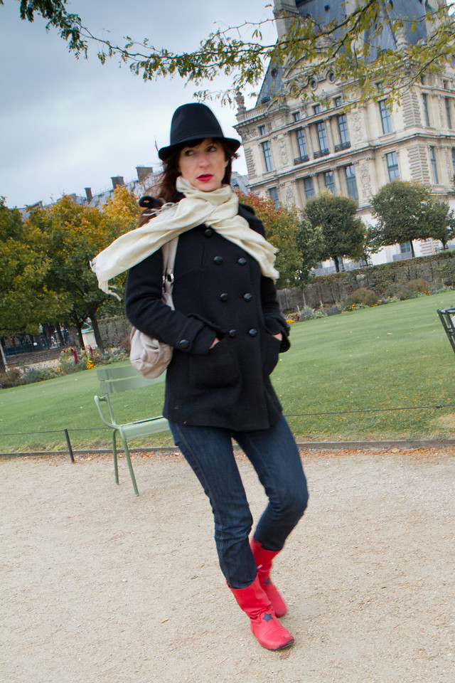A woman of fashion strolls in the Tuileries garden outside the Louvre