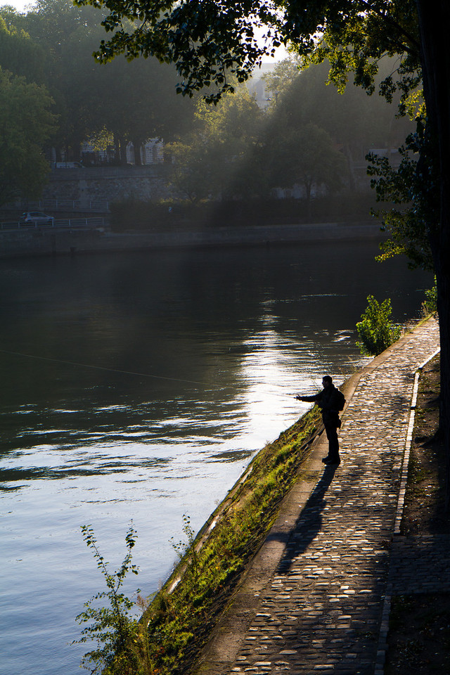 A fisherman along the Seine after sunrise