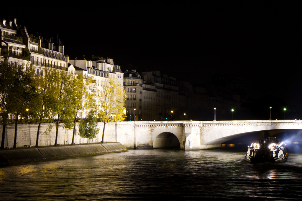 Bateaux Mouche, boats for tourists shining their bright lights on the Ile St. Louis from the Seine. The buildings on the isle were mainly built in the 1600's