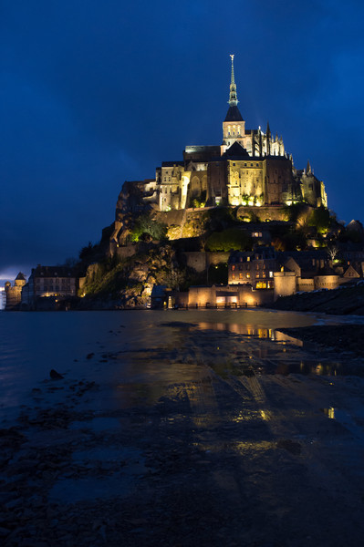 Mont St Michel at dusk, taken from the lower parking lot on the causeway (which is almost covered with the tide)