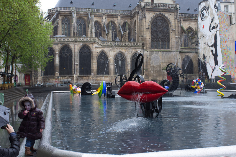 Back in Paris, we had rain again. This young girl is imitating for her mom the wall mural you see on the right side of the photo. This is the fountain in front of the Pompidou museum of modern art.