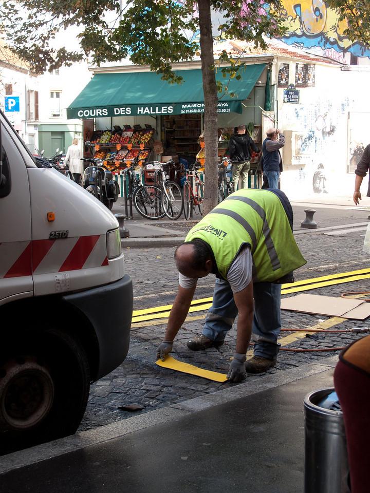 Putting down street markings on cobble stones. Heat, apply, heat again.