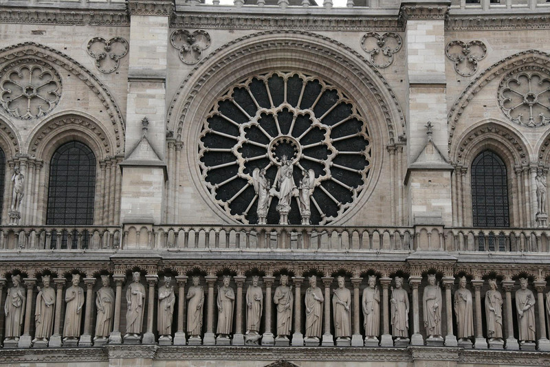 Notre Dame facade. Lots of sculptures high above the street, loaded with meticulous detail.