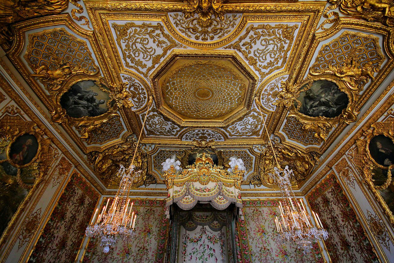 The Queen's bed chamber, Palace at Versailles. All of these rooms were large. During the 1789 riot/revolt at the Palace, the Queen slipped away from the mob through a slender door on the left, hidden by the gold and white wall panel.