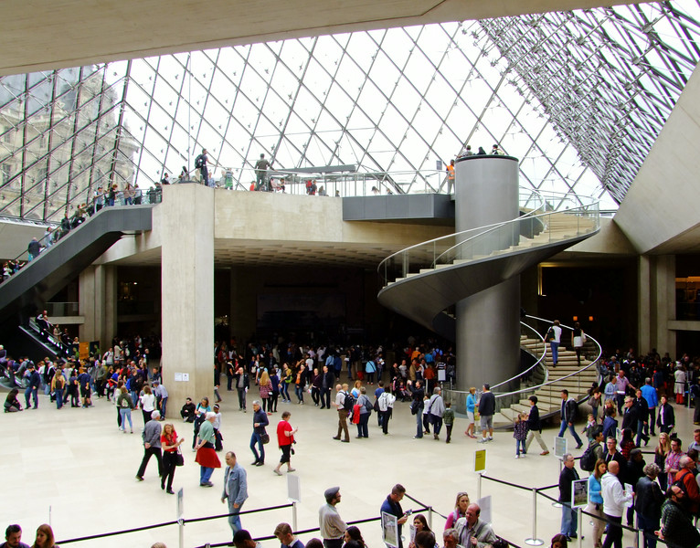 Interior of the Louvre under the modern glass pyramid.  The metal cylinder raises and lowers as a guard tower.