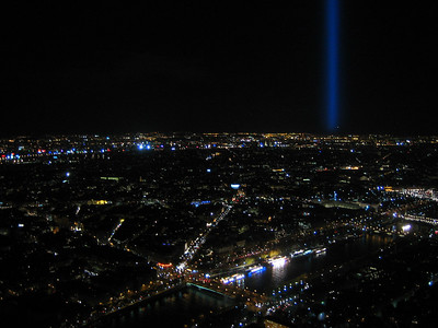 A strong beam shines from the top of the Eiffel Tower.