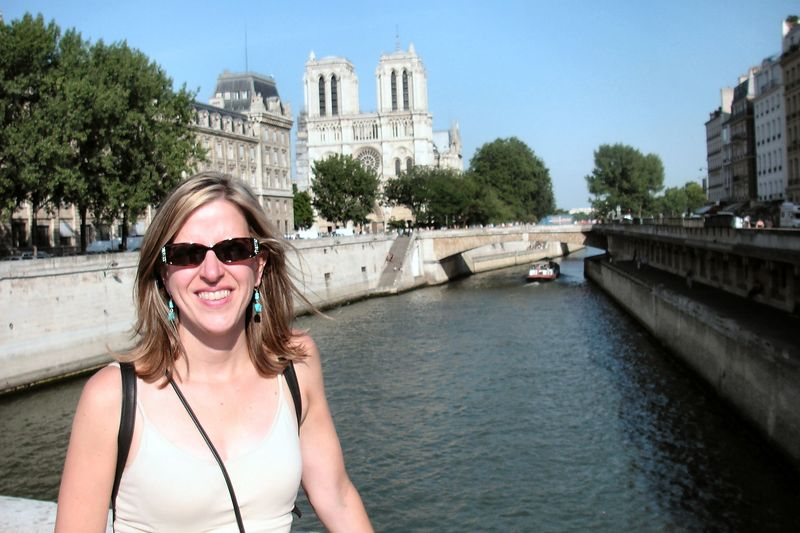 Elizabeth on a bridge across the Seine River with Notre Dame in the distance.