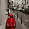 red scooter parked on a street in Paris