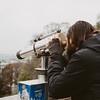 man looking through telescope overlooking the city of Paris