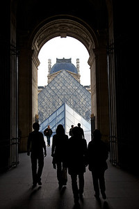 Approaching Art:  Through the Louvre Corridor These shadowy figures are walking to the Louvre glass pyramid, a portal for art lovers worldwide.
