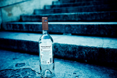 An empty bottle of wine sit alone on some steps.