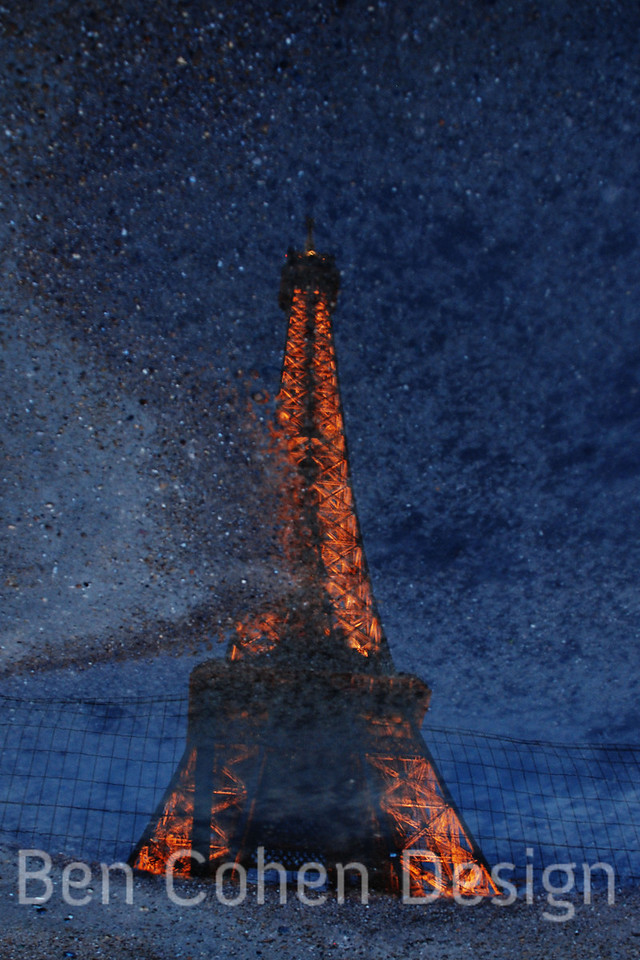 The Eiffel Tower captured in a puddle.