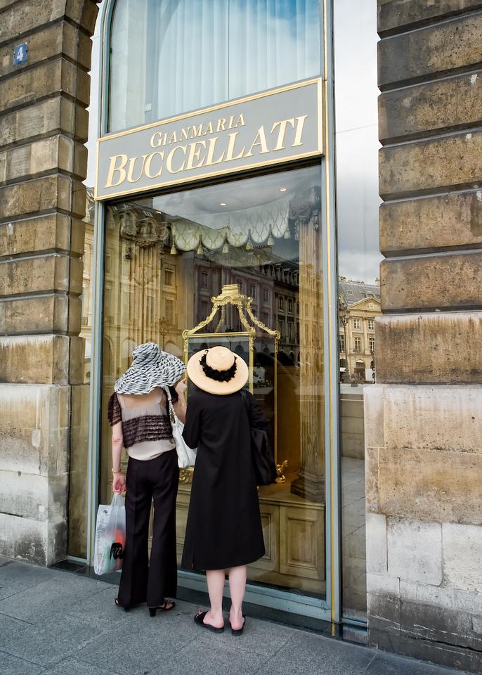 Two women window shop near the Ritz Hotel in Paris.