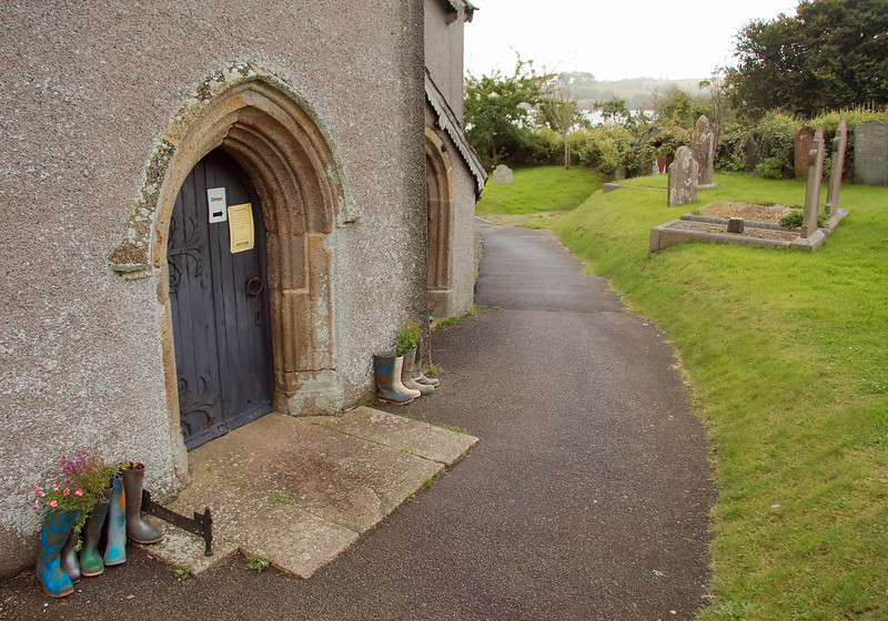 "North entrance to the church. Local gardeners seem to enjoy turning ""Wellies"" into flower pots."